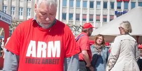 """Mann mit T-Shirt """"Arm trotz Arbeit"""""""