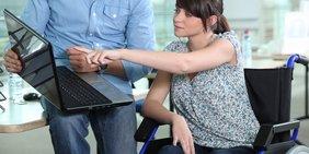 Junge Frau im Rollstuhl deutet mit dem Zeigefinger auf einen Laptop; Hintergrund: männliche Person / Bürokontext