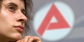Eine Jugendlsiche vor einem Logo der Arbeitsagentur