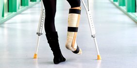 Frauenbeine mit Krücken, gebrochenes Bein im Gips